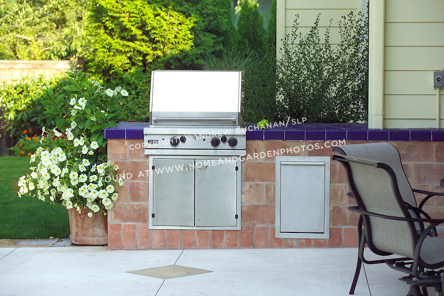 Vignette of a built-in stainless steel gas grill and blue tile-topped counter work area, surrounded by a decorative concrete and tile edged patio.