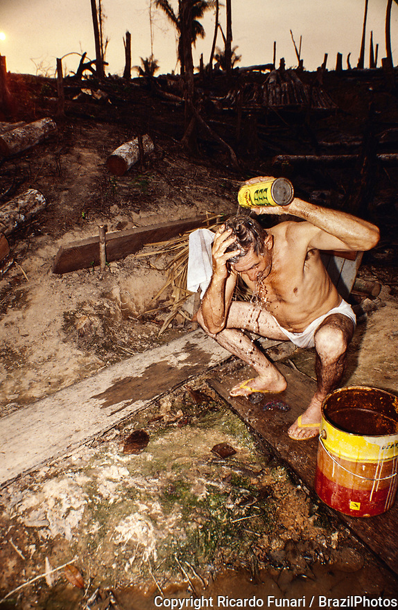 Degrading labor, man washes himself using a can of water at the end of a tough working day clearing the forest, Amazon deforestation. Acre State, Brazil.