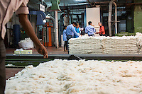 Fairtrade personnel being given a tour as raw cotton is being processed using a machine in the Blow Room of the Pratibha vertically integrated garment unit in Indore, Madhya Pradesh, India on 11 November 2014. Photo by Suzanne Lee for Fairtrade