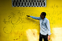 A young Somali immigrant, heading to the southern U.S. border, translates Arabic script writings on the wall of the detention center in Metetí, Darién, Panama, 31 January 2015.