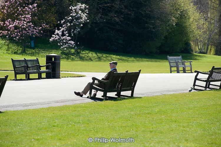 Elderly man sitting on a bench, Regent's Park, London.