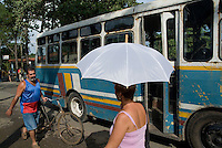 Bus driving past a man with a bicycle and a woman holding an umbrella, Vinales, Cuba.