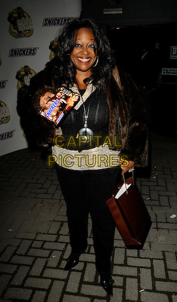 "KYM MAZELLE.The ""No Nuts! No Entry!"" Snickers party, The Arches bar & nightclub, Southwark St., London, England..February 26th, 2009.full length kim brown goody bag fur jacket necklace silver black trousers chocolate food.CAP/CAN.©Can Nguyen/Capital Pictures."