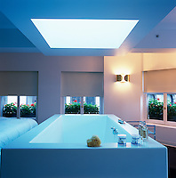 The huge bath is made from white Corian on a steel frame and is positioned conveniently at the end of the bed