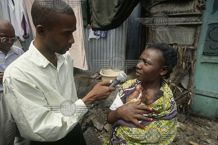 © Giacomo Pirozzi / Panos Pictures..COMOROS..A community radio reporter interviewing a young mother.