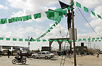 A Palestinian Hamas supporter hangs green Islamic flags as decoration ahead of the upcoming prisoner swap, at the entrance to the Rafah border crossing, southern Gaza Strip, Monday, Oct. 17, 2011. The exchange between Israel and Hamas in which 1,027 Palestinian prisoners will be released for captured Israeli soldier Gilad Schalit is slated to take place on Tuesday. . Photo by Abed Rahim Khatib