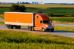 An orange truck and trailer is speeding across the Illinois prairie on I-57 near Gilman, IL.