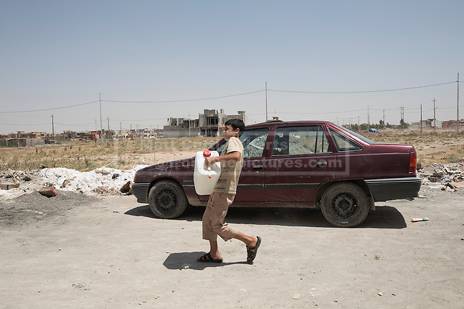 A young Iraqi Christian refugee from Mosul hauls a water container from a tanker provided by Kurdish Zeravani soldiers in Hamdaniyah, Iraq.