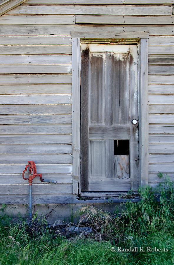 Weathered door and red pump, near St. John, Palouse region of Eastern Washington.