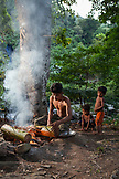 PHILIPPINES, Palawan, Barangay region, chicken being prepared and cooked over an open fire in Kalakwasan Villagen Noli with his two sons