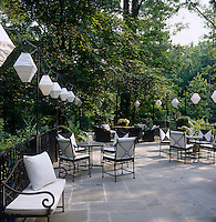 Paper lanterns are strung around this flag-stoned terrace which is furnished with an assortment of wrought-iron seating