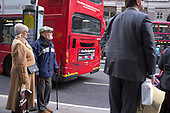 Peope waiting at a bus stop in The Strand, London.