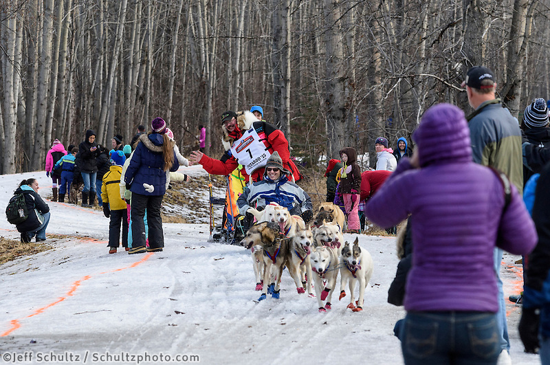 Alan Eischens and team run past spectators on the bike/ski trail with an Iditarider in the basket during the Anchorage, Alaska ceremonial start of the 2015 Iditarod race. Photo by Ed Bennett/IditarodPhotos.com