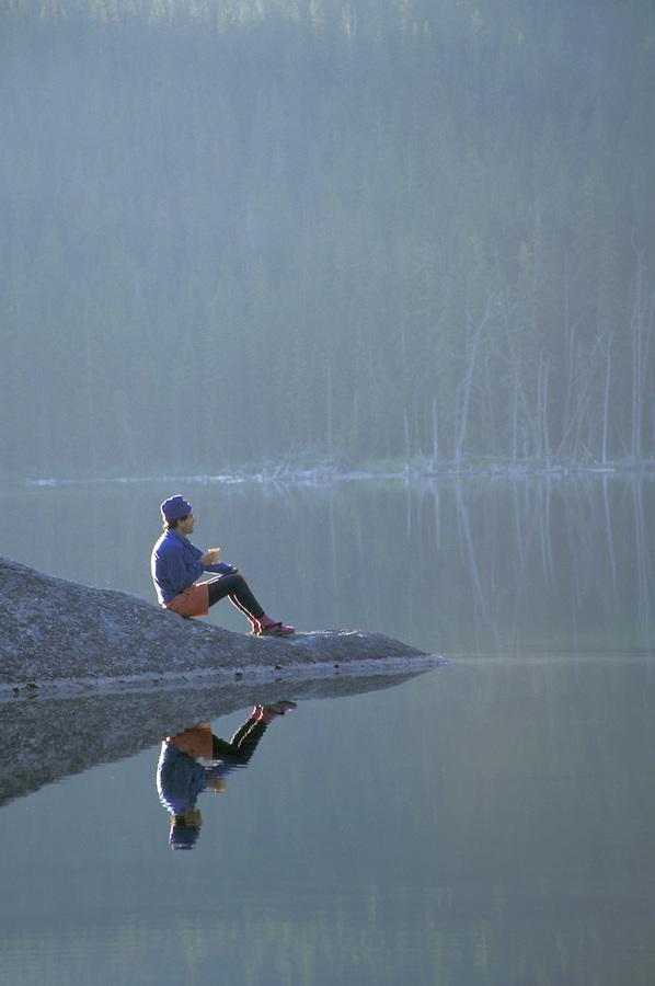 Man sitting on rock reflected in mountain lake, Enchantment Lakes, Washington