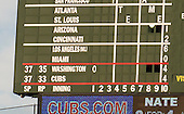 Close-up view of the iconic, hand-operated scoreboard at Wrigley Field showing the openings at right where the operators watch the game during the tenth inning of the game between the Washington Nationals and the Chicago Cubs on Thursday, August 22, 2013.<br /> Credit: Ron Sachs / CNP