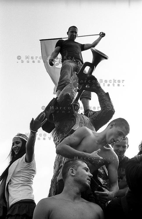 Festival di trombe e ottoni di Guca (Cacak). Gente sulla statua del trombettista e un uomo con la bandiera della Serbia --- Trumpet festival of Guca (Cacak). People over the trumpeter's statue and a man with the flag of Serbia