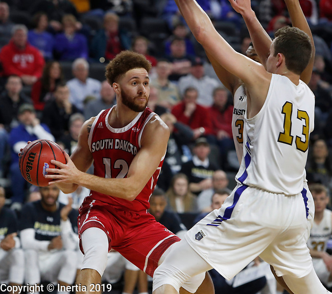 SIOUX FALLS, SD - MARCH 10: Trey Burch-Manning #12 from South Dakota seeks an opening around Matt Holba #13 from Purdue Fort Wayne at the 2019 Summit League Basketball Tournament at the Denny Sanford Premier Center in Sioux Falls. (Photo by Dick Carlson/Inertia)