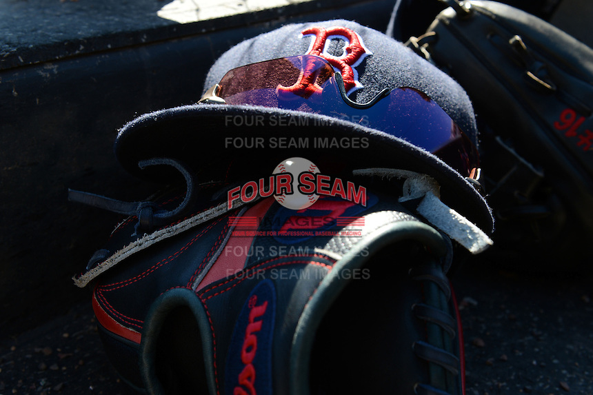 Boston Red Sox hat with sunglasses sits on a glove in the dugout during a spring training game against the Baltimore Orioles on March 8, 2014 at Ed Smith Stadium in Sarasota, Florida.  Baltimore defeated Boston 7-3.  (Mike Janes/Four Seam Images)