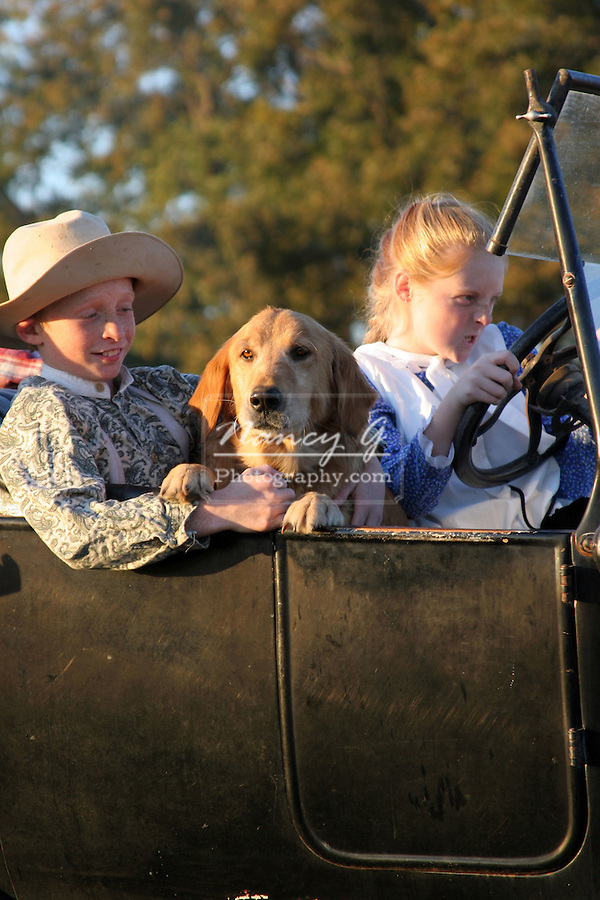 A young boy and girl with a red dog driving in an old car