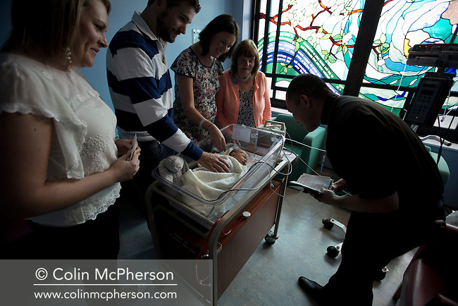 Philip and Kathryn Jones from Canterbury, Kent, pictured with their three-day-old son Finn in a room at the Evelina London Children's Hospital neonatal intensive care unit in central London taking part in a blessing with members of their family. Their son was born with a pre-diagnosed condition which required a life-saving, five-hour heart 'switch' operation to be carried out within the first two weeks of his life. The operation, which took place when Finn was 10 days old was successful, however, due to other near fatal complications the his recovery during the subsequent six weeks was slow and difficult.
