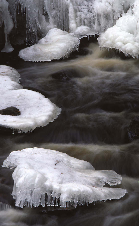A long exposure shows frigid water flowing between ice-covered rocks near Priest Lake, Idaho.