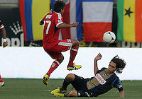 CHESTER, PA - AUGUST 12, 2012:  Gabriel Farfan (15) of the Philadelphia Union slides under  Pavel Pardo (17) of the Chicago Fire during an MLS match at PPL Park, in Chester, PA on August 12. Fire won 3-1.