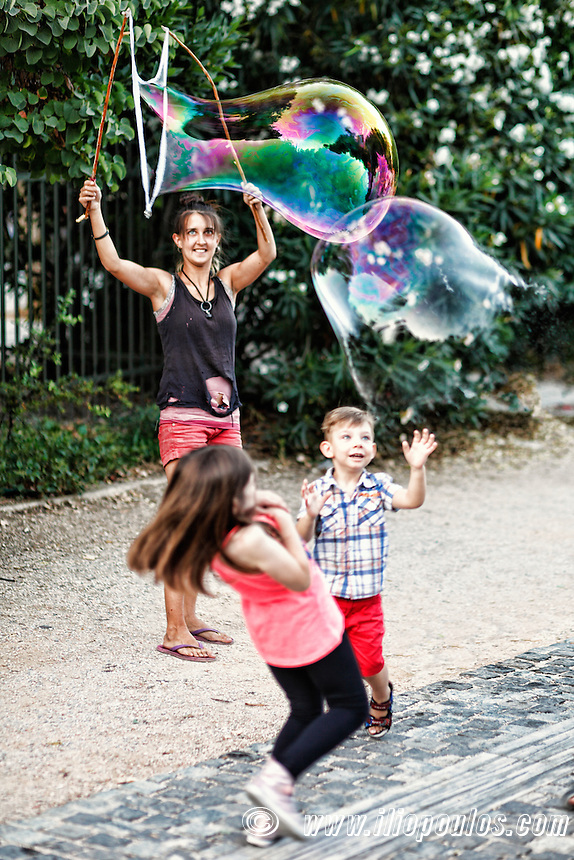 Little children playing with giant bubbles in the streets of Athens, Greece