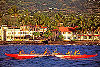 Women and men paddlers in red canoes race in the ocean off Kona on the Big Island of Hawaii.