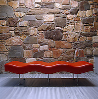 A sculptural Undulatus Bench by Stanley Jay Friedman is placed against a stone wall backdrop