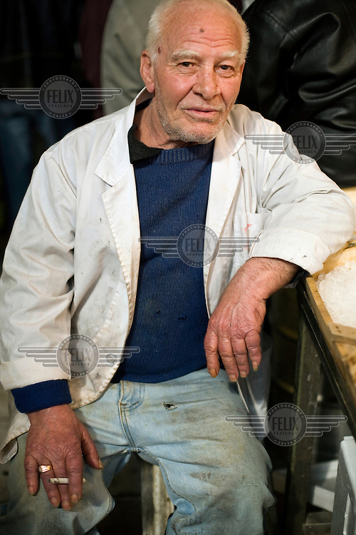 An elderly fishmonger takes a break to smoke a cigarette by his stall in the Athens Central Market on Athinas Street.