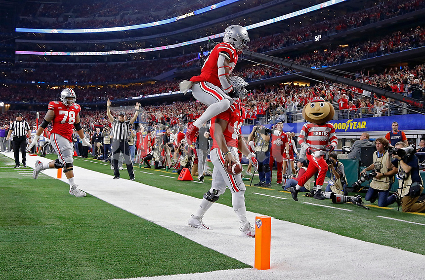 Ohio State Buckeyes quarterback J.T. Barrett (16) scores on a running touchdown and celebrates with Ohio State Buckeyes running back Mike Weber (25) against USC Trojans in the 1st half at the 82nd Goodyear Cotton Bowl Classic at AT&T Stadium in Arlington, Texas on December 29, 2017.  [Kyle Robertson/Dispatch]