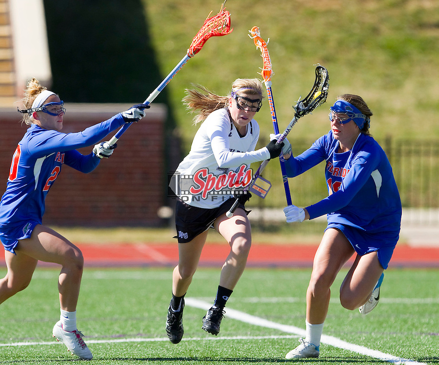Mackenzie Carroll (4) of the High Point Panthers tries to run between Kayla Stolins (20) and Sydney DuPre (18) of the Florida Gators during first half action at Vert Track, Soccer & Lacrosse Stadium on February 17, 2013 in High Point, North Carolina.  The Gators defeated the Panthers 13-7.   (Brian Westerholt/Sports On Film)