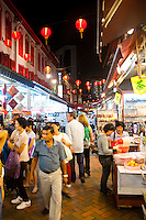 Chinatown Street Market at Night, Singapore. The street market in Chinatown comes alive at night, with an endless selection of foods to try and market stalls competing eagerly for tourists to buy their souvenirs.