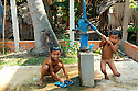 SREY BREY VILLAGE, CAMBODIA--Boys take turns bathing at a well donated to their village by a Muslim aid agency. Many foreigners come to Cambodia to pressure Imam San Cham to adopt a stricter, more mainstream form of Islam. PHOTO BY JODI HILTON