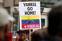 NEW YORK, NY - FEBRUARY 23: A man holds a placard as he attends a Pro-Venezuelan Government protest and against the US military intervention in latin america on February 23, 2019 in Wall street New York.  (Photo by Kena Betancur/VIEWpress)
