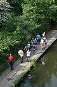 London, UK. 28.05.2016. A group of photographers walks along the canal towpath in Regent's Park on a sunny Bank Holiday weekend in May. Photograph © Jane Hobson.