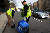 Lionel Hampton (left) and David Dollosa fill potholes with asphalt while working for the Boston Public Works Department in Boston, Massachusetts, USA, on April 12, 2012. The city uses a computer system to track public complaints and record work done by city crews to mitigate these complaints.  A supervisor or inspector photographs before and after pictures of the work in addition to making notes about the work done.