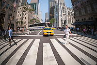 A taxi stops at a crosswalk on Fifth Avenue in New York on Thursday, September 3, 2015. Because of the rise in Uber and other apps taxi medallions have decreased in worth to about $900,000 with loan delinquencies on the rise. The Melrose Credit Union has $168 million in delinquencies as of May 2015 while in January 2014 it had only $32,000. In the next six months Melrose has $212 million in maturing loans which many owners will be unable to pay.   (© Richard B. Levine)