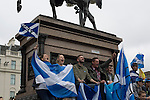 A group of people with Scottish saltire flags sitting on a statue at a pro-independence gathering in George Square, Glasgow. The gathering brought together Yes Scotland supporters who favour Scotland leaving the union with the United Kingdom. On the 18th of September 2014, the people of Scotland voted in a referendum to decide whether the country's union with England should continue or Scotland should become an independent nation once again and leave the United Kingdom.