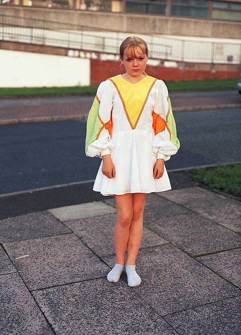 HATTERSLEY, UK - Nicole, a member of the Hattersley Youth Morris Dancers group wears an outfit designed and hand-made by parents on the Hattersley Estate.. .The Hattersley Estate was created in the early 1960s to house residents displaced by the slum clearances of inner city Salford and Manchester and soon gained notoreity between 1963 and 1965 as the home to the Moors Murderers, Myra Hindley and Ian Brady. Lying in a relatively isolated area on the edge of the Pennines, residents today continue to wait for the investment and infrastructure promised to them decades ago. In the gap between promise and reality, a unique characted formed during years of adversity continues to thrive on the estate.