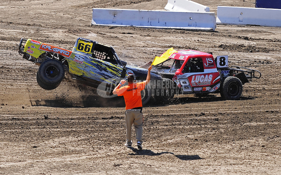 Jun. 26, 2009; Lake Elsinore, CA, USA; LOORRS unlimited lite driver Leroy Loerwald (right) gets hit by Kyle LeDuc as a flagman waves the caution flag during practice prior to qualifying. Mandatory Credit: Mark J. Rebilas-