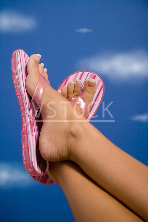 Woman wearing flip flops holding crossed legs up against sky