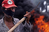 Riot, demonstration for land reform. MST - Movimento Sem Terra ( Landless Workers Movement ), Brazil. Violence against the authority, anger, rage. Rural workers block road in Bahia State. Burning of tires.