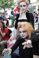 2 female participants in prague zombie walk may 2014. One wearing a red collar with a lead that the other woman is holding, woman in front holding her arms in front of her, sitting down, the other standing up in the background.
