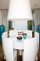 In a bedroom suite at the Villa Bianca in Iniala a modern dining area is dominated by a huge ceiling light
