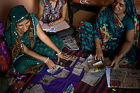 Women learn how to stitch a blouse from 11am to 3pm from a Fairtrade Premium funded stitching class taught by Kavita Yadav in Maheshwar, Khargone, Madhya Pradesh, India on 13 November 2014. Stitching teacher Kavita, 34, travels to a different village every few weeks to conduct the stitching course that is free for women (whether Fairtrade-associated or not), as she is funded using the Fairtrade Premiums from Fairtrade cotton farmers. Photo by Suzanne Lee for Fairtrade