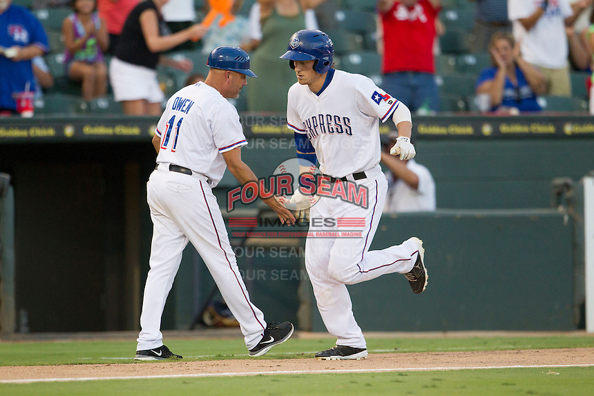 Round Rock Express outfielder Jim Adduci (24) is greeted by third base coach Spike Owen (11) after hitting a home run against the Oklahoma City RedHawks during the Pacific Coast League baseball game on August 25, 2013 at the Dell Diamond in Round Rock, Texas. Round Rock defeated Oklahoma City 9-2. (Andrew Woolley/Four Seam Images)