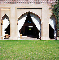 The loggia is shaded by curtains hung across the arches that open on to the garden
