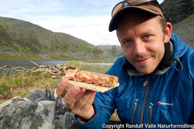 Mann spiser knekkebrød med laksefilet. ---- Man eating bread and salmon filet.