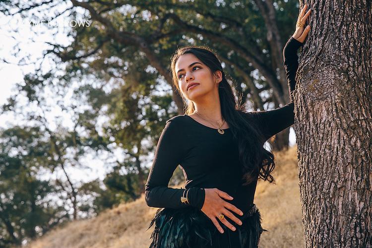 Fine art portrait of a beautiful Latina woman wearing a black dress with feathers.